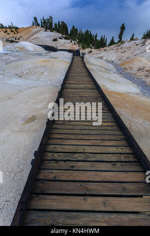 Safety of the boardwalk assures visitors to the  dangerous steam of  boiling springs and hot mud pots in Lassen - Stock Photo