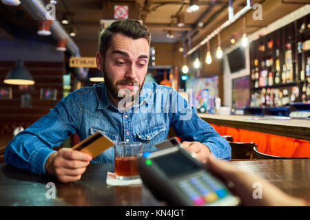 Drunk Man Paying via Credit Card in Pub - Stock Photo