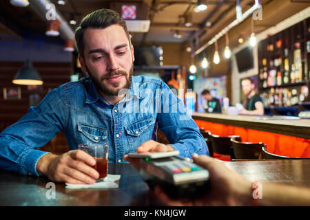 Drunk Man Paying via NFC in Pub - Stock Photo