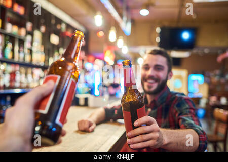 Happy Young Man Clinking Bottles with Friend in Bar - Stock Photo