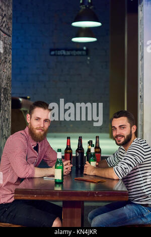 Two Buddies Drinking Beer in Bar - Stock Photo