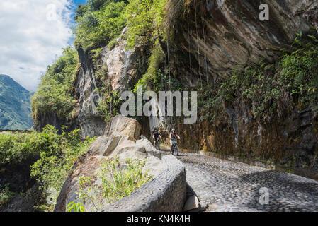 Cascades route, Banos - Puyo, Ecuador - December 8, 2017: Tourists ride bicycles along the Waterfalls Road over - Stock Photo