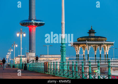 NIght falls on Brighton seafront, UK. Victorian Bandstand and i360 tower in the distance. - Stock Photo