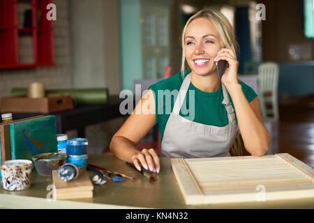 Female Artist Speaking by Phone in Workshop - Stock Photo
