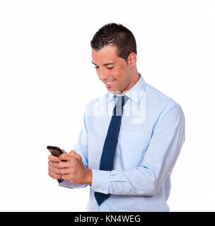 Portrait of a handsome hispanic guy sending a message with his mobile on isolated background. - Stock Photo