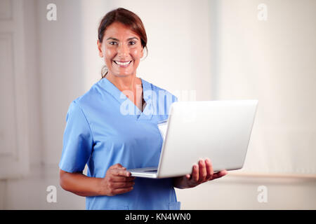 Portrait of a professional female doctor holding a laptop while standing and smiling at you on hospital. - Stock Photo