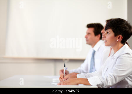 Portrait of a pretty hispanic executive looking at presentation in front of a coworker on office background - copyspace. - Stock Photo
