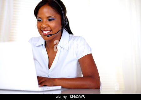 Attractive young call center operator working on laptop and speaking on microphone - copyspace. - Stock Photo