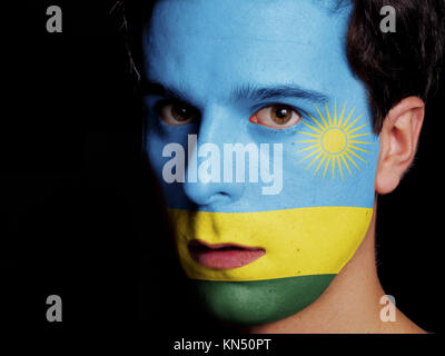 Flag of Rwanda Painted on a Face of a Young Man. - Stock Photo