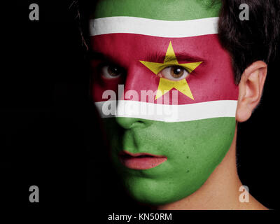 Flag of Suriname Painted on a Face of a Young Man. - Stock Photo