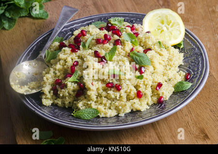 Moroccan lemon and pomegranate couscous topped with mint. - Stock Photo