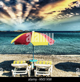Colourful beach chairs with straw umbrellas on a beautiful sandy beach. - Stock Photo
