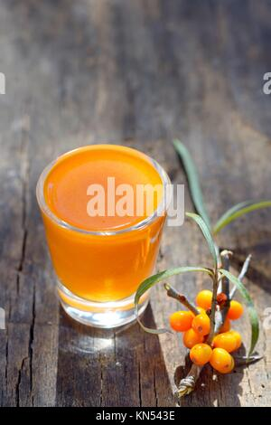 Sea buckthorn juice and berries isolated on wooden background. Natural detox. - Stock Photo
