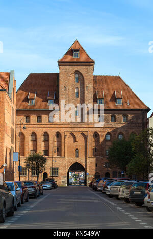 Cars on the Szeroka Street and Crane (Zuraw) Gate at the Main Town (Old Town) in Gdansk, Poland, on a sunny day. - Stock Photo
