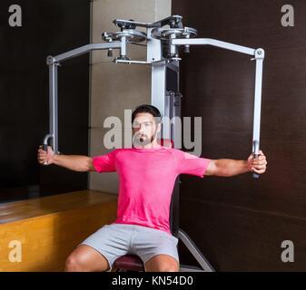 pec-deck fly flies pec deck chest workout man exercise at gym. - Stock Photo