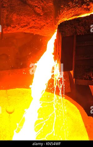 Foundry - molten metal poured from ladle for casting. - Stock Photo