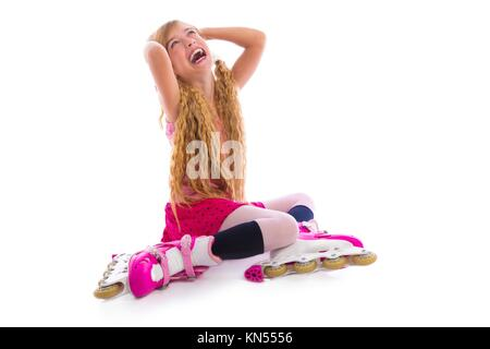 blond pigtails roller skate girl sitting laughing happy on white background. - Stock Photo