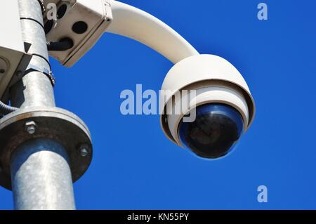 Hi-tech dome type camera over blue sky. - Stock Photo