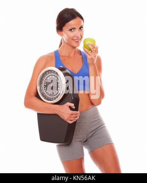 Sporty young woman eating apple to lose weight and looking at you against white background. - Stock Photo