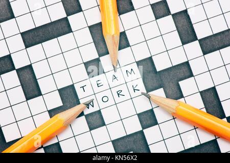 Closeup of crossword puzzle and three pens pointing to the word teamwork. Conceptual image of problem solving, finding - Stock Photo