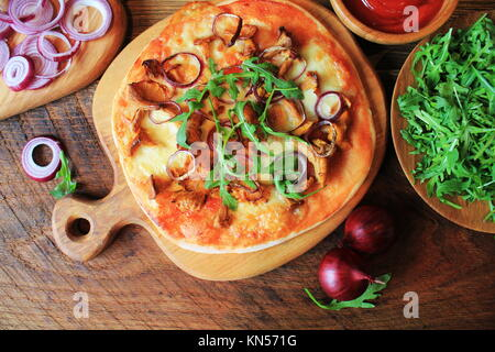 Hot homemade pizza with mushrooms chanterelle, rucola on wooden table. Top view - Stock Photo