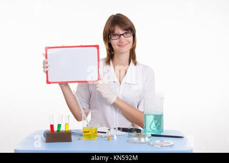 Young beautiful girl posing chemical experiments in the laboratory. - Stock Photo