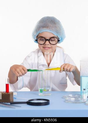 Chemist girl sitting at the table with the reagents in chemistry class and puts experiments. - Stock Photo