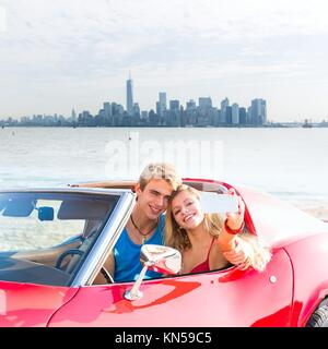 selfie of young teen couple at convertible car in New York Manhattan skyline photo mount. - Stock Photo