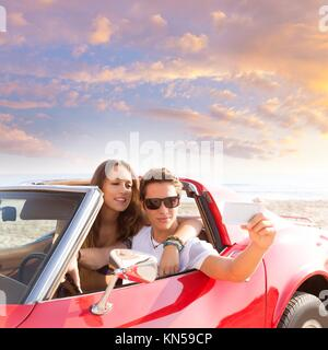 selfie photo of young teen couple in convertible sports car. - Stock Photo