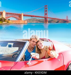 selfie of young teen couple at convertible car in San Francisco Golden Gate Bridge photo mount. - Stock Photo