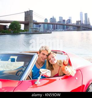 selfie of young teen couple at convertible car in New York Brooklyn Bridge photo mount. - Stock Photo