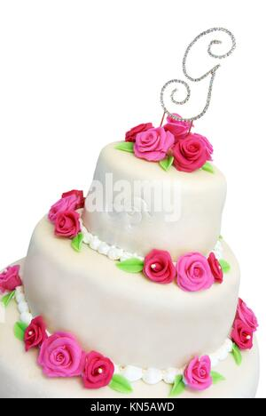 Three tiered wedding cake covered in marzipan and decorated with pink marzipan roses. - Stock Photo