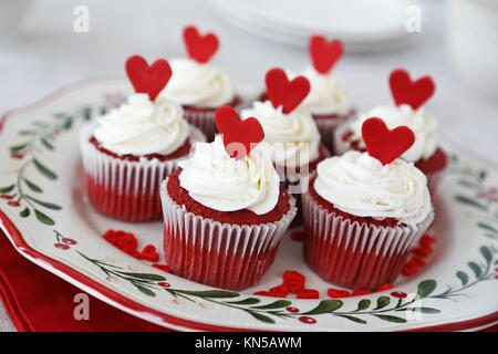 Red velvet cupcakes decorated for Christmas with red hearts. - Stock Photo