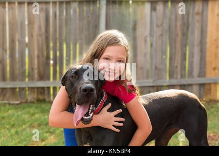 great dane and kid girl hug playing together at backyard outdoor. - Stock Photo