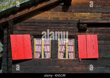 Windows with red shutters of a Swiss chalet, Belalp, Valais, Switzerland. - Stock Photo