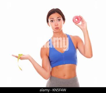 Slim lady choosing between sugar and fitness with donut on left hand and measuring tape on right hand against white - Stock Photo