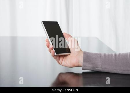 woman hand grey sweater finger touching digital phone mobile blank screen on black reflect table white curtain indoor. - Stock Photo