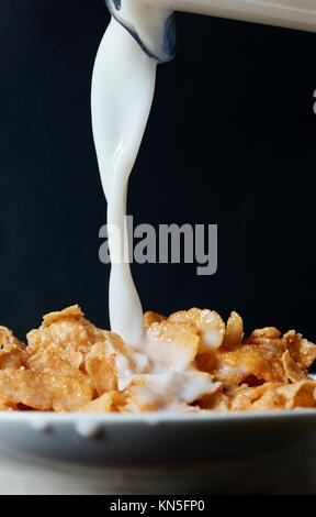 Corn flakes breakfast with milk being poured over it. - Stock Photo