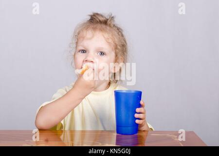 Two-year-old girl sitting at the table, eating a muffin and drinking from a plastic Cup. - Stock Photo