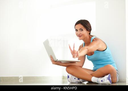 Fit woman in sports clothing doing the victory sign with fingers while looking at you - copyspace. - Stock Photo