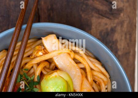 hand pulled stretched Chinese ramen noodles on a bowl with chopstick. - Stock Photo