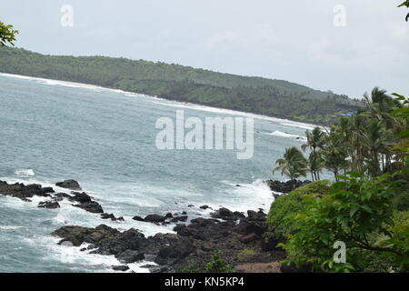 Sea and mountain view. Ocean and mountain. Rocky sea view with coconut trees in side. Sea surrounded by greenery - Stock Photo
