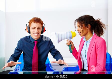 business woman talking in megaphone african ethnicity to young executive. - Stock Photo