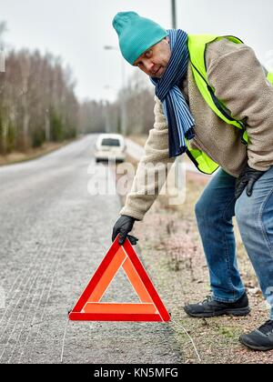 Mid adult man wearing reflector vest and he have a red warning triangle - road and vehicle on background. - Stock Photo