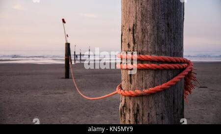 strong red rope on wooden stake. - Stock Photo