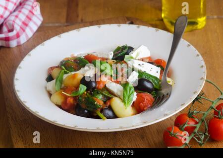 Gnocchi with feta, black olives and cherry tomatoes topped with basil. - Stock Photo