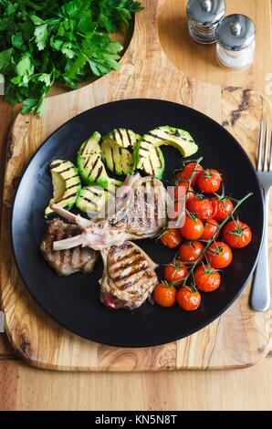Griddled lamb cutlets with avocado and cherry tomatoes. - Stock Photo