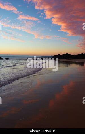 Colourful sunrise clouds reflected on Porthgwidden Beach, St Ives, Cornwall, England, Europe. - Stock Photo