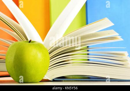 Composition with hardcover books and apple in the library. - Stock Photo