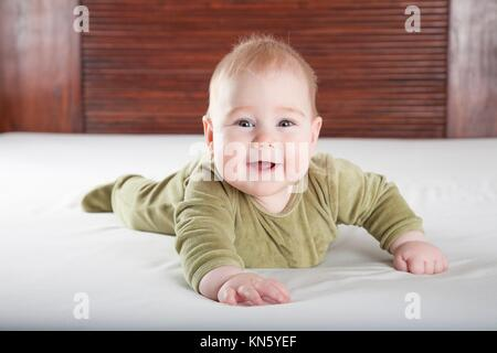 six months age blonde baby green velvet onesie lying on white sheet bed with brown wood background smiling happy - Stock Photo
